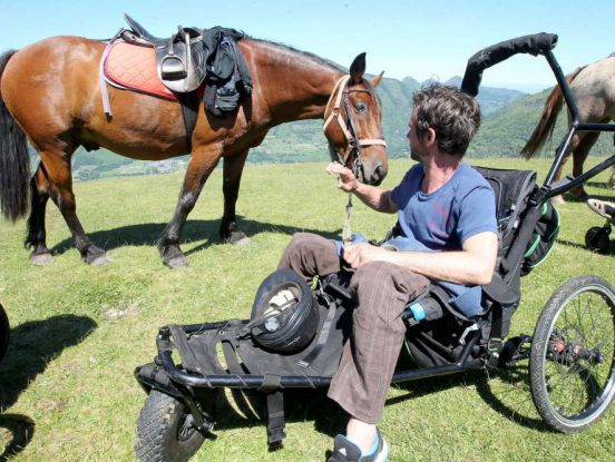 Fauteuil roulant pour randonnée devant un cheval